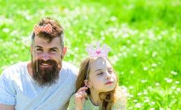 Семья тратит отдых outdoors, игры игры girlish Ребенок и отец представляя с атрибутами будочки кроны и фото смычка Стоковые Фотографии RF