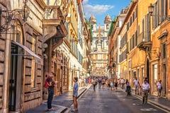 Семья туристов внутри через dei Condotti, улицу водя к Аркаде di Spagna и испанские шаги стоковое изображение