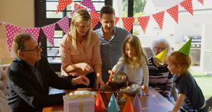 Семья украшая именниный пирог в живя комнате 4k акции видеоматериалы