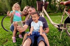 семья усмехаясь пока принимающ автопортрет в парке стоковое изображение rf
