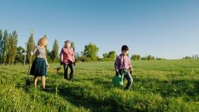 Семья фермеров с малым сыном идет засадить дерево Садовые инструменты медведя и саженцы яблони акции видеоматериалы