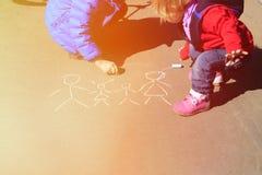 Семья чертежа мальчика и девушки с мелом дальше Стоковое Изображение