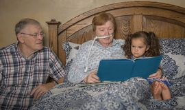 Семья читает с женщиной на кислороде стоковые изображения rf