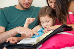 Семья читая библию совместно Стоковое Изображение