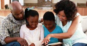 Семья читая книгу в живущей комнате 4k видеоматериал