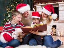 Семья читая книгу перед рождественской елкой Стоковые Фотографии RF