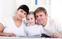Семья читая книгу совместно Стоковые Фотографии RF