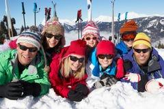 Семья 2 имея потеху на празднике лыжи в горах