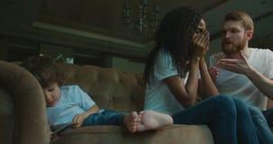 Семья Multirace имеет конфликт пока маленький сын играет на мобильном телефоне и лежит на софе эмоционально сток-видео