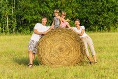 Семья outdoors имеет остальные на сене Стоковая Фотография