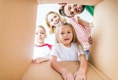 Семья peeking от картонной коробки Стоковое Изображение