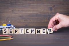 сентябрь Деревянные письма на предпосылке стола офиса, информативных и связи Стоковая Фотография RF