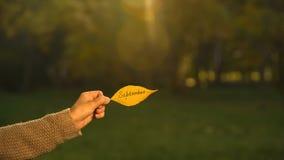 Сентябрь написанный на лист осени, руке держа сочинительства, золотой сезон падения стоковое изображение