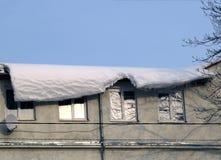 Сень снега которая опасно висит вниз от крыши Стоковая Фотография