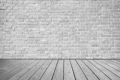 Серая кирпичная стена на деревянном поле Стоковое Изображение