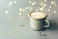 Серая кружка металла с кофе, золотыми звездами и bokeh стоковая фотография