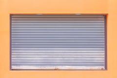 Серая свертывая стальная дверь или дверь шторки ролика с padlock на оранжевой предпосылке стены, картинах металла стоковое изображение