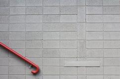 Серая стена шлакоблока с красным рельсом руки стоковые фотографии rf