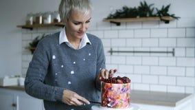 Серая с волосами женщина режет с ножом небольшую часть от красивого торта, десерт украшена с ягодами дальше акции видеоматериалы