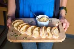 Сервер держа деревянный поднос с свеже испеченным хлебом и домодельным маслом Руки женщин с деревянным сервером закусок стоковое фото rf