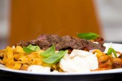 Сервировка зажаренных стейка и макаронных изделий говядины Стоковое Фото