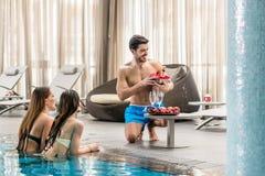 Сервировка молодого человека с шампанским 2 женщины на бассейне Стоковые Изображения RF