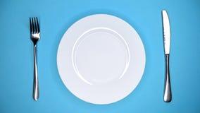Сервировка стола в ресторане или кафе Вилка и нож Женские руки кладут и принимают отсутствующую белую плиту от голубой таблицы видеоматериал