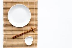 Сервировка стола для крена суш Пустая плита на циновке около палочки и шара для sause на белом взгляд сверху предпосылки Стоковое Фото