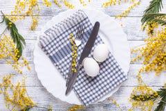 Сервировка стола пасхи Белые яйца, салфетка на плите, цветки мимозы, вилка, нож на деревянном столе стоковые фотографии rf