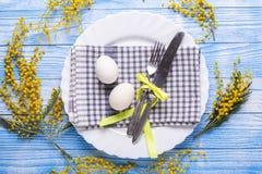 Сервировка стола пасхи Белые яйца, салфетка на плите, цветки мимозы, вилка, нож на голубом деревянном столе стоковое изображение