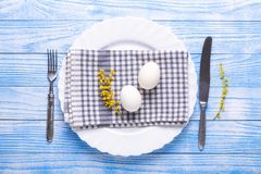 Сервировка стола пасхи Белые яйца, салфетка на плите, цветки мимозы, вилка, нож на голубом деревянном столе стоковое фото