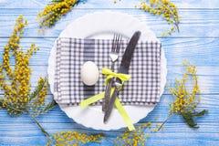 Сервировка стола пасхи Белые яйца, салфетка на плите, цветки мимозы, вилка, нож на голубом деревянном столе стоковые фотографии rf