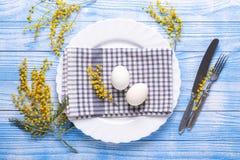 Сервировка стола пасхи Белые яйца, салфетка на плите, цветки мимозы, вилка, нож на голубом деревянном столе стоковые изображения