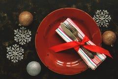 Сервировка стола рождества, пустая красная плита, винтажный столовый прибор на темной деревенской предпосылке украшенной со снежи стоковое фото
