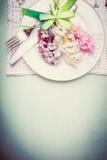 Сервировка стола весны с плитой, столовым прибором, лентой и милыми гиацинтами цветет, взгляд сверху, граница, пастельная Стоковые Фото