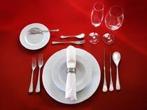 Сервировка стола на красной предпосылке Стоковое Фото