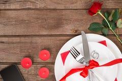 Сервировка стола обедающего дня ` s валентинки с красной лентой, подняла, нож и кольцо вилки над предпосылкой дуба Стоковые Фотографии RF