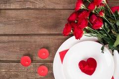 Сервировка стола обедающего дня ` s валентинки с красной лентой, розы, нож и вилка звенят над предпосылкой дуба Стоковое Изображение