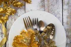 Сервировка стола рождества в золоте и коричневый тон на деревянном столе Стоковое Фото