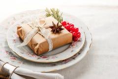 Сервировка стола рождества с настоящим моментом, ягодами и специями Стоковые Изображения