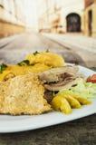 Сервировка традиционного эквадорского fritada типичная с кожей свинины, мясом, tortillas картошки на белой плите Стоковое Изображение RF