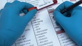 Сердечная отметка, доктор проверяя имена в пробеле лаборатории, показывая пробу крови в трубке акции видеоматериалы