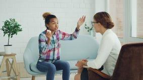 Сердитая Афро-американская дама говорит с психологом и жалуется с стороной осадки и показывать пока специалист видеоматериал