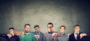 Сердитая группа в составе молодые человеки показывая большие пальцы руки вниз показывать Стоковые Фото