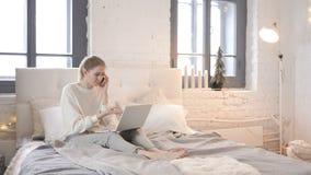 Сердитая девушка говоря по телефону пока сидящ в кровати, бой акции видеоматериалы