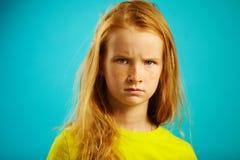 Сердитая девушка детей с красными волосами на сини стоковые изображения