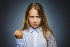 Сердитая девушка на серой предпосылке стоковое фото rf