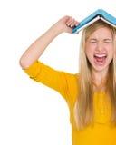 Сердитая девушка студента с книгой надземной Стоковое фото RF