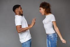 Сердитая женщина крича на человеке над серой предпосылкой стоковая фотография
