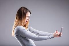 Сердитая женщина против ее телефона Стоковое Изображение RF